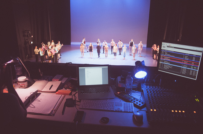 Photo: Harry Butcher. A typical QLab setup for stage sits high in the stands as a group of performers rehearse on stage