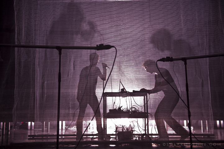"Photo: Marc Solaris. ""...interaction between video, sound and movement"" Through a stage curtain there is an outline of a person singing into a microphone as an other person controls the mixing console"