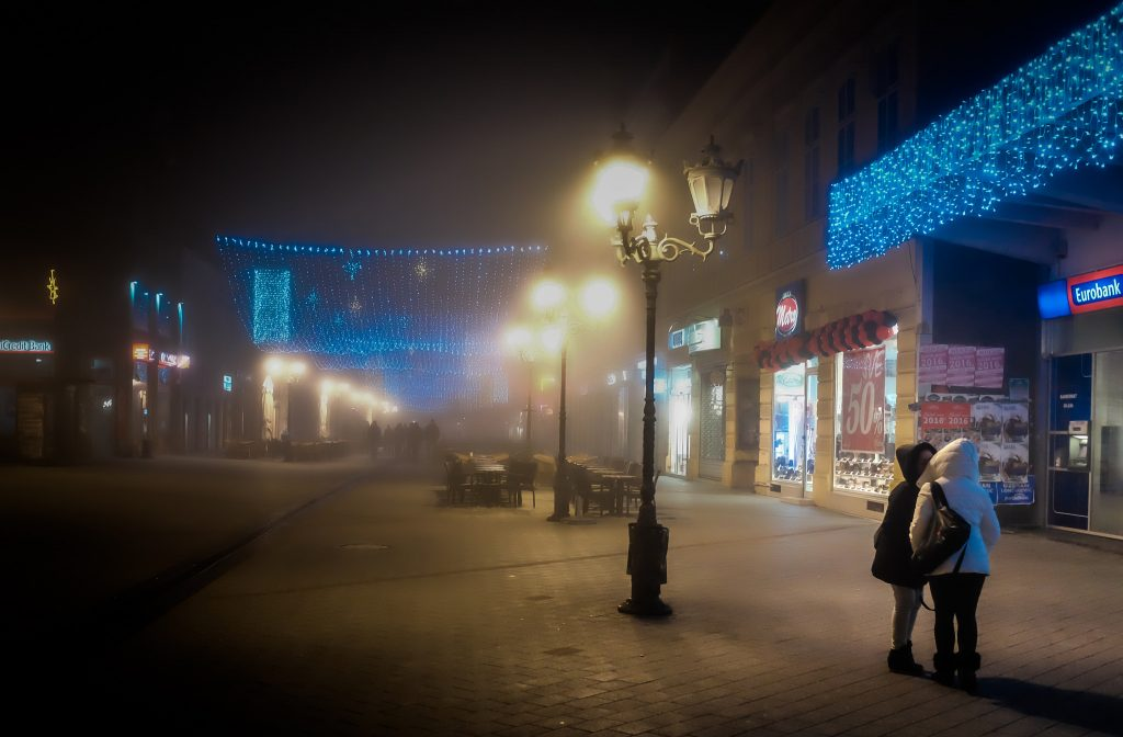 Two women kiss on a foggy European destination street with blue and white light displays, secluded from the others walking down the road. Article by Adriane Kuzminski.