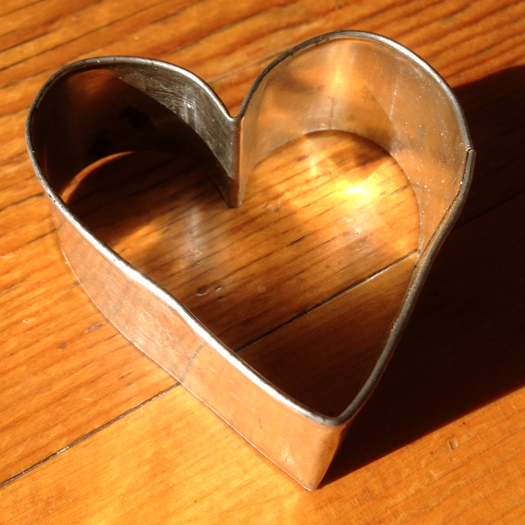 A heart-shaped cookie cutter sits on a wooden table.