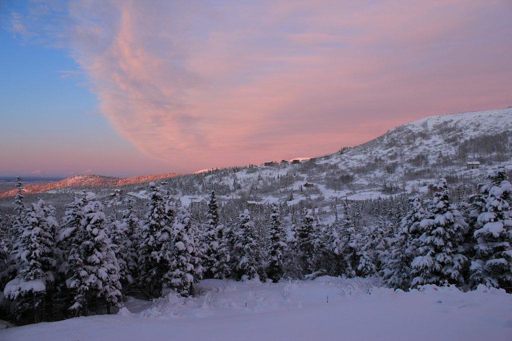 Dusk sets over rolling hills populated by log cabins and pines freshly burdened with snow.