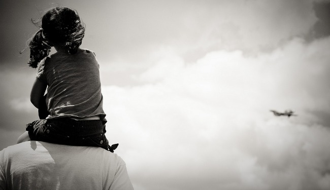 A little girl sits atop her father's shoulders, staring off into the clouds.
