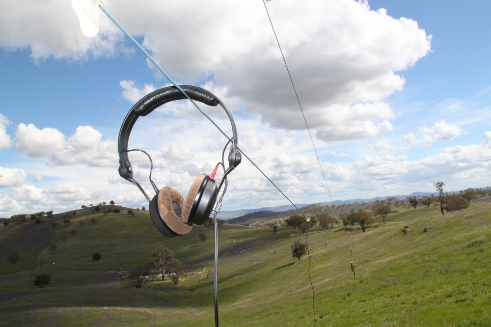 A pair of headphones hang on a long line in a rolling field. Article by Adriane Kuzminski.