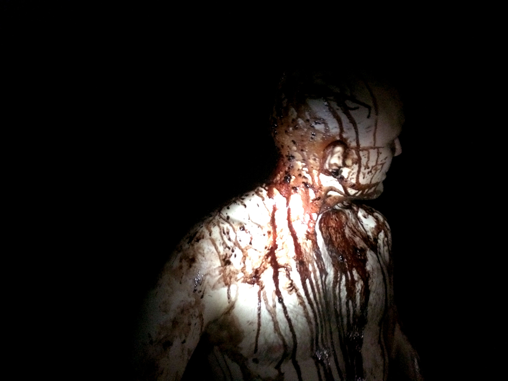 A man stands in the dark covered in pig's blood.