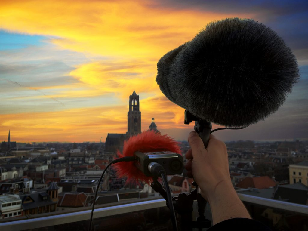 A boom mic and digital recorder sit at the edge of a rooftop facing a dusk sky over a city in the Netherlands. Article edited by Adriane Kuzminski.