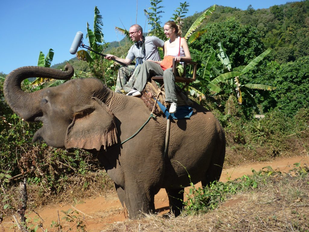 Two people ride an elephant in Thailand. The man holds a boom mic near the elephant's head as it trumpets. Article edited by Adriane Kuzminski.
