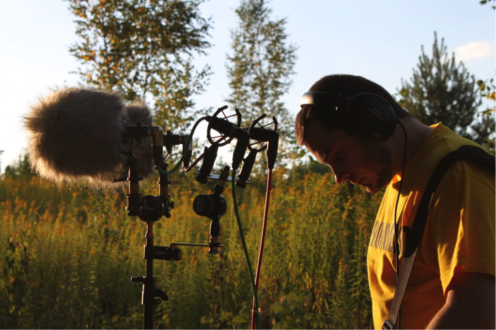Serj stands next to his mic, listening with headphones, in the middle of a field. Article edited by Adriane Kuzminski.