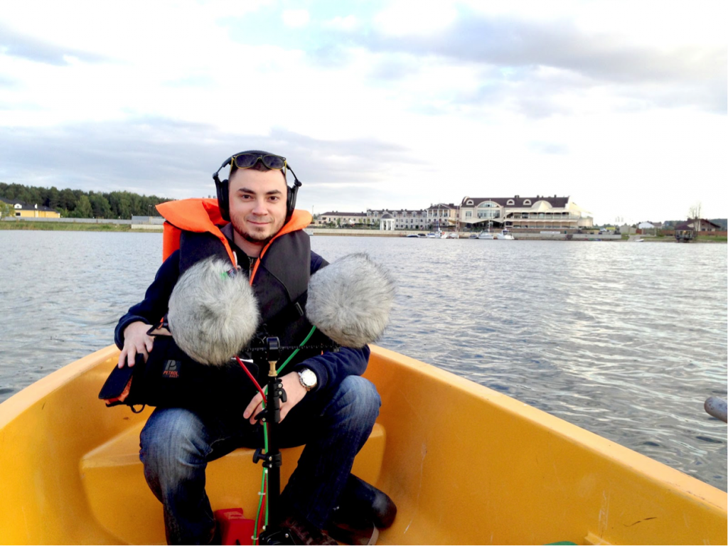 Serj sits in a canoe on a lake with his mic setup.