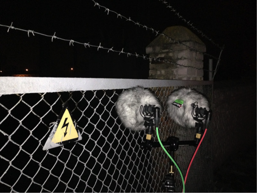 A pair of mics face a buzzing electric and barbed-wire fence.