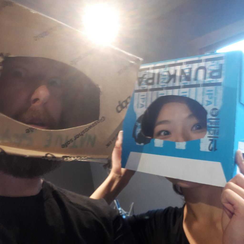 Jeff and Mimi have some fun in the Foley studio by sliding cut-out boxes over their heads.
