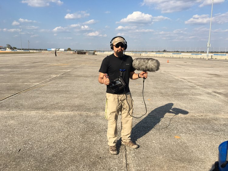Watson Wu holds a boom mic and gives the thumbs up on the tarmac.