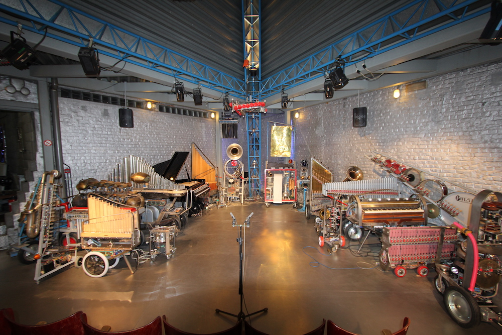 Dozens of robotic orchestral instruments line the walls of an industrial performance space. Article written by Adriane Kuzminski.