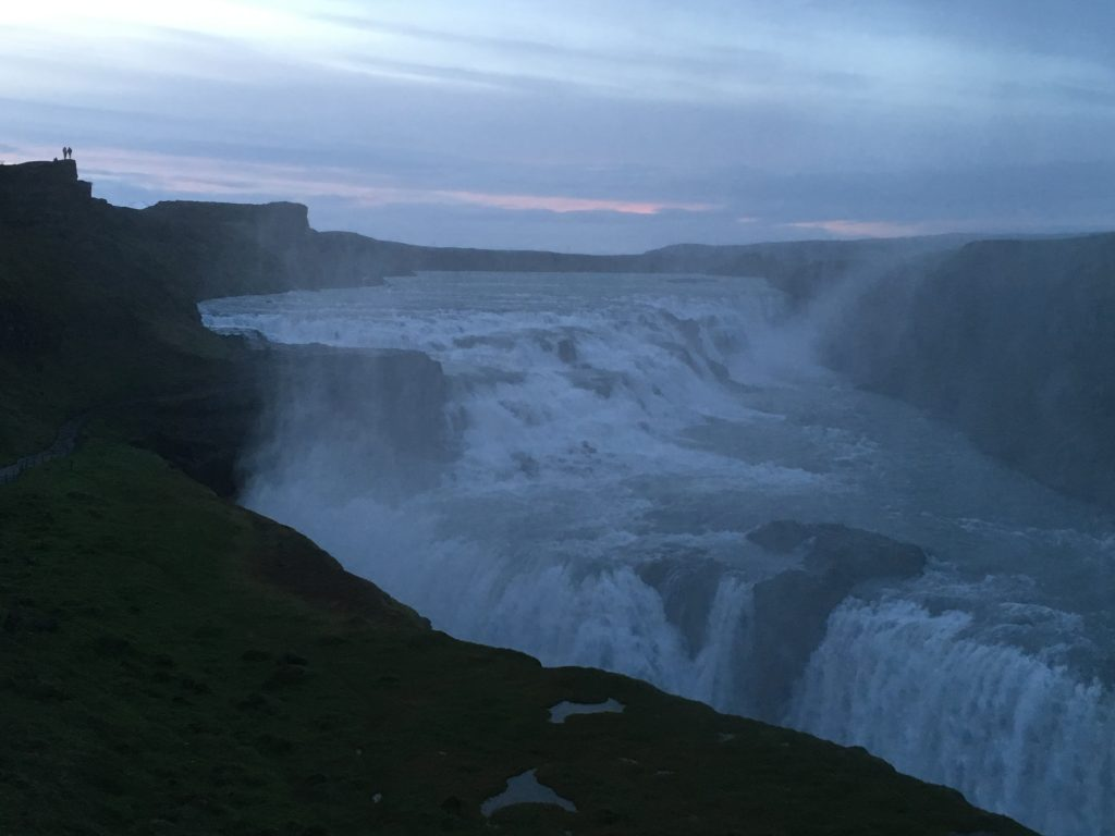 A distant shot of the Gullfoss waterfall in Iceland, with two small human figures in the top-left for scale.