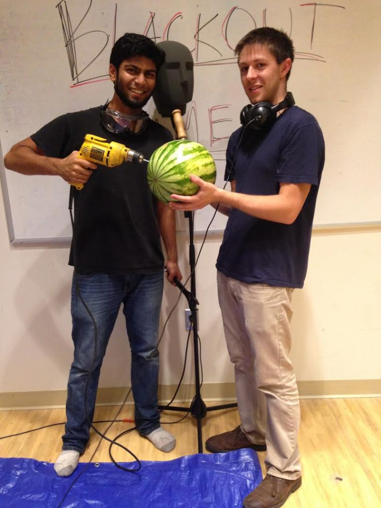Kedar puts a drill into a watermelon as someone else holds it.