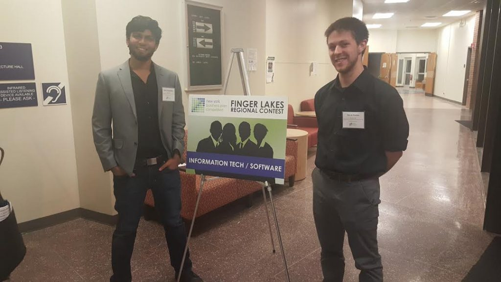 Kedar and his team mate stand with name tags next to a sign for the Finger Lakes Regional Contest.